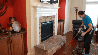 How to Clean a Gas Fireplace, Angela Brown Vacuuming Around Fireplace