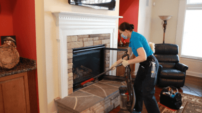 How to Clean a Gas Fireplace, Angela Brown Vacuuming Under Fireplace