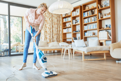 Spin Mop vs. a Steam Mop for Hardwood Floors, Woman with Steam Mop on Wood Floor